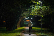 One Young Adult Woman In White Jacket Walking On Sidewalk Through Alley Of Trees Under Lamp Light In Autumn Night. Spending Time Alone In Nature. Peaceful Atmosphere. Back View.