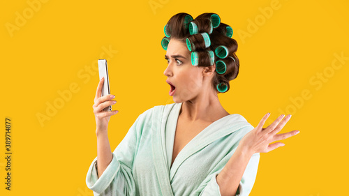 Fotografía Shocked Housewife Holding Phone Reading Shocking Message, Yellow Background, Pan