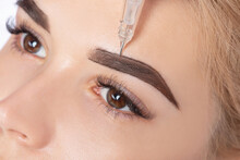Permanent Make-up For Eyebrows Of Beautiful Blonde Woman In Beauty Salon. Closeup Beautician Doing Eyebrows Tattooing.