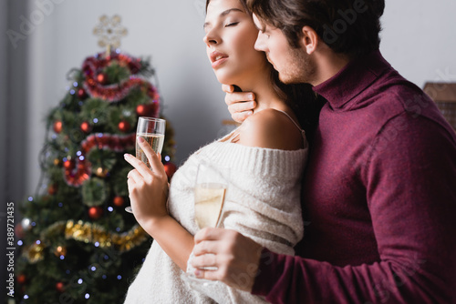 couple holding glasses with champagne and hugging near christmas tree on blurred Canvas