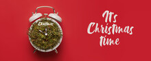 Conceptual Holiday Alarm Clock With Hands Of The Clock And Spruce Branches And Lettering It's Christmas Time On A Red Background