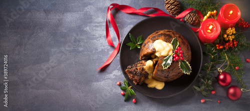 Foto Richly spiced Christmas pudding cake with custard and Christmas decorations
