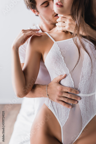 passionate man embracing sensual girlfriend in white and sexy bodysuit