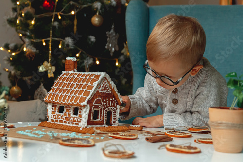 Little boy decorates christmas gingerbread house Canvas