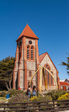Stanley, Falkland Islands, UK - December 15, 2008: Frontal View On Red And Brown Stone Christ Church Cathedral With Tower Under Blue Sky In Its Garden With Green Tree And Whalebone Arch..