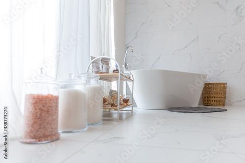 Foto bain blanc dans une pièce de marbre avec lumière du jour diffuse par des rideaux