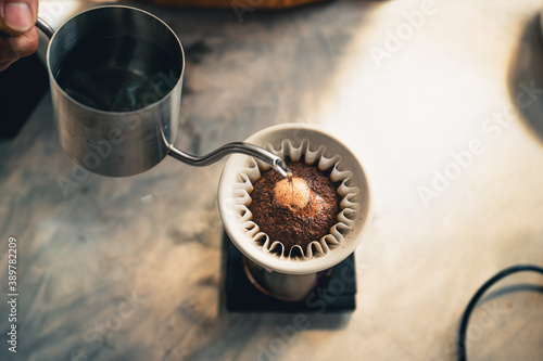 Drip coffee, barista pouring water on coffee ground with filter Fotobehang