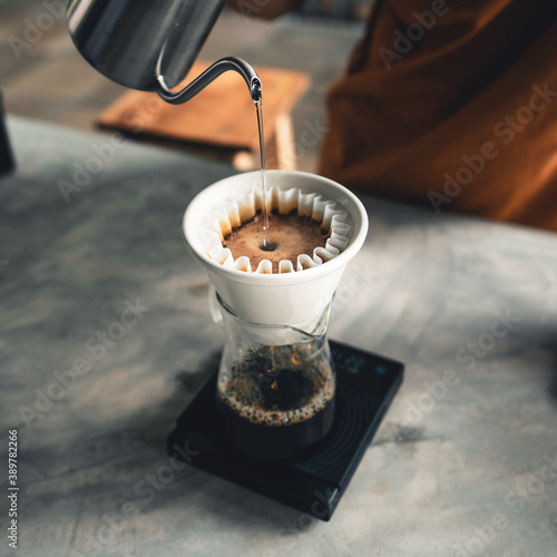 Fotografia Drip coffee, barista pouring water on coffee ground with filter