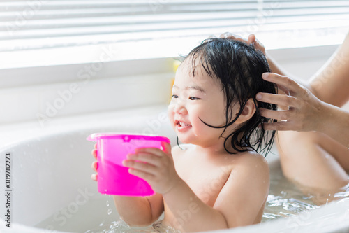 Foto Cute Asian kid toddler having a bath cleaning bathing bath tub with mother, pare
