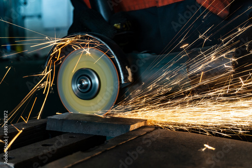 Angle grinder at work, sparks and dust from the cut-off stone. Fotobehang
