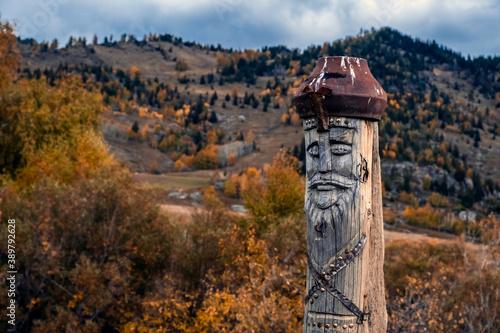Leinwand Poster Wooden totem pillar on mountains background in autumn