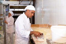 Skilled Hispanic Bakery Worker Portioning Dough With Scraper And Weighing Pieces