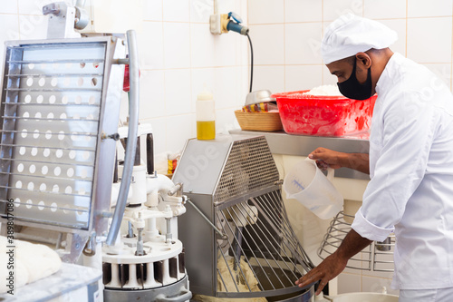 Papel de parede Professional hispanic baker controlling process of making bread dough in kneadin