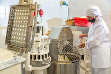 Young Female Bakery Worker Controlling Dough Kneading On Professional Equipment