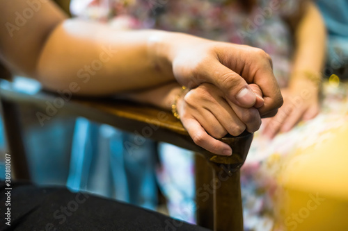 Fotografie, Obraz Closeup on two young lovers holding hands at a table, symbol sign sincere feelings, compassion, loved one, say sorry