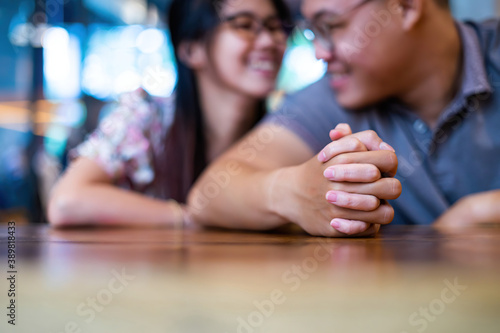 Closeup on two young lovers holding hands at a table, symbol sign sincere feelings, compassion, loved one, say sorry Wallpaper Mural