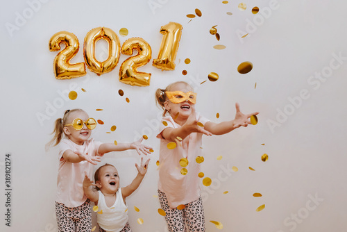 Obraz Three little girls are enjoying the flying golden confetti. Celebrating at home 2021. Concept for Christmas and New Year. - fototapety do salonu