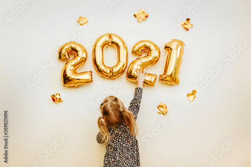 Fotografiet Little girl decorates the wall of the house with golden numbers 2021