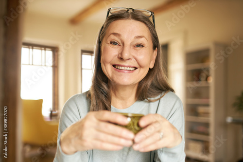 Obraz Rest, relaxation and comfort concept. Indoor shot of joyful positive gray haired female on retirement having relaxed carefree facial expression, enjoying hot tea, holding mug in both hands - fototapety do salonu