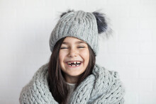 Happy Laughing Child Girl In Winter Knitted Hat And Scarf Hat At Studio
