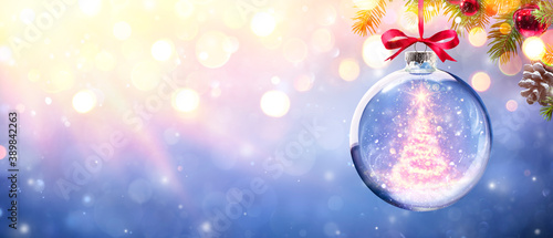 Obraz Shiny Christmas Tree In Glass Sphere Hanging On Pine Branch With Defocused Lights - fototapety do salonu
