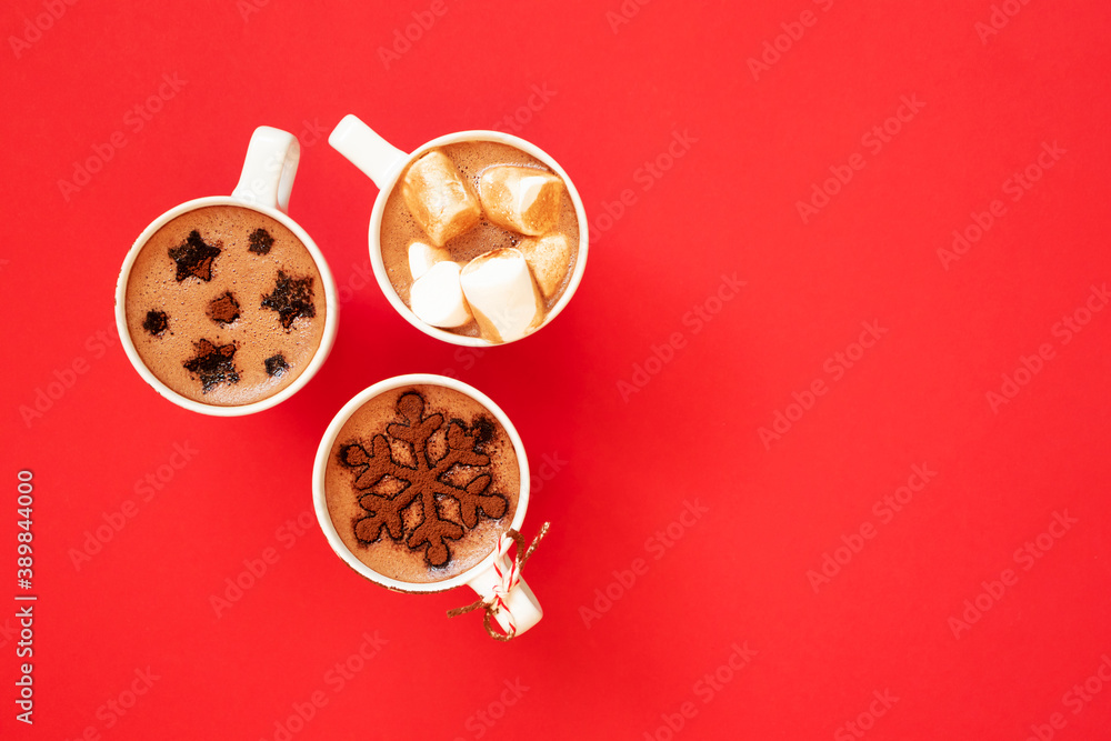 Fototapeta Hot chocolate with marshmallows and cocoa powder decor in white cups on red background