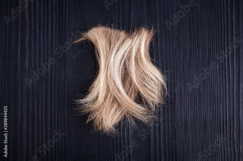 Tela Blond wavy hair lock black wooden background close up, cut off natural blonde ha