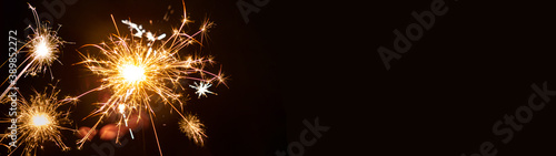 Silvester / New year background - People hold sparkling sparkler in her hand at dark night