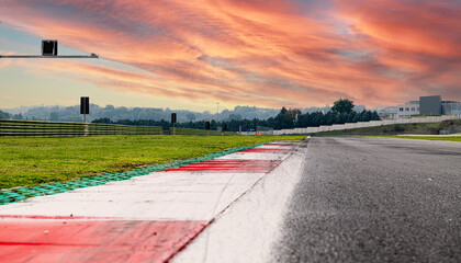 Sunrise sky over asphalt straight track motorsport circuit scenic background curb surface level
