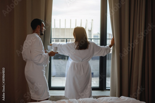 Man and a woman in white robes by the window. Canvas Print