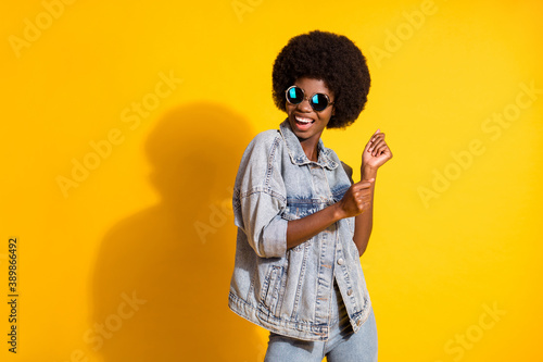 Photo of lovely young woman wear casual jeans clothes dancing looking empty space isolated yellow color background