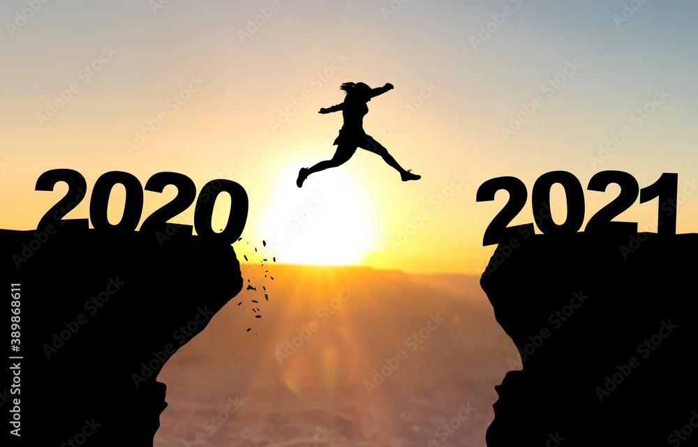 Fototapeta Frau spring über Abgrund vor Sonnenuntergang mit der Beschriftung 2020/2021.