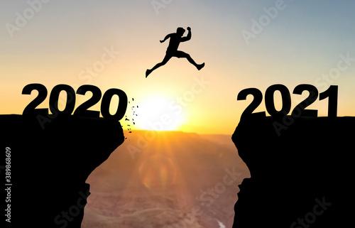 Mann spring über Abgrund vor Sonnenuntergang mit der Beschriftung 2020/2021 Fototapet