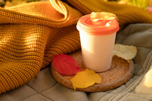 Autumn Mood, Relaxation Alone, Positive Thoughts, Picnic Concept. Paper Cup Of Hot Drink With An Orange Lid Stands On A Cork Tray With Fallen Leaves. Quilt, Knitted Yellow Sweater On The Background.