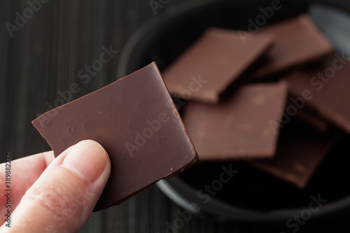 Man holding a piece of broken dark chocolate Fototapeta