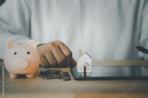 Fototapeta Man use digital pen for planning family future and tablet, miniature home and pink piggy bank