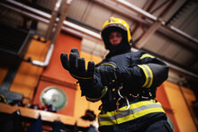 Closeup Of Fireman Putting On Gloves And Preparing For Action While Standing In Fire Station.