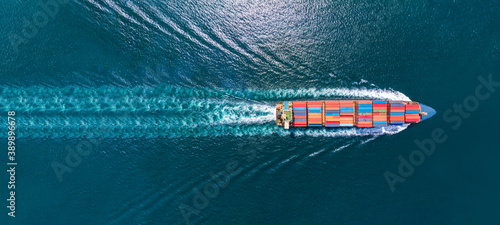 Fototapeta Aerial top view of cargo ship with contrail in the ocean sea ship carrying conta