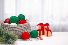 Green And Red Yarn In A Knitted Gray Basket On A White Table. Home Comfort And Christmas Concept. Women's And Men's Hobby Knitting.