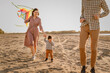 Happy family walking on sandy beach of river. Father, mother holding baby son on hands and playing with kite.