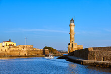 Fishing Boat Pass By Famous Lighthouse And Walls Of Old Port, Firka Fortress, Old Venetian Harbour Of Chania, Crete, Greece In Morning. Golden Hour