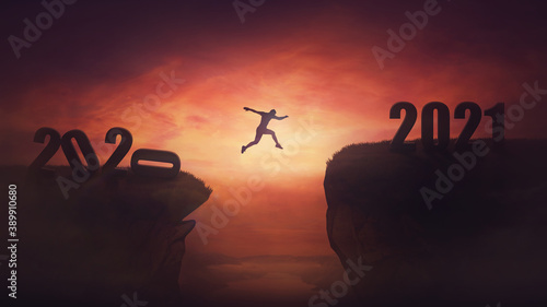 Fotografiet Surreal view, man jumping over a chasm obstacle between old 2020 and new 2021 years