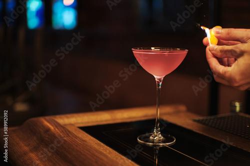 Fotografiet Pink Cosmopolitan vodka cocktail with flame