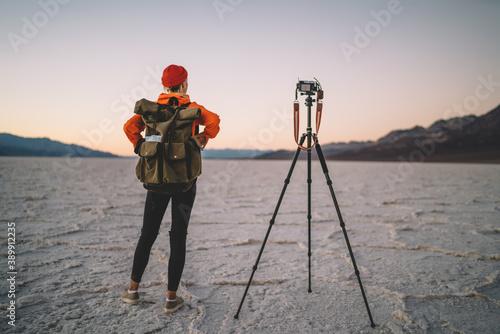 Female explorer enjoying landscape of dry desert with photography equipment Canvas