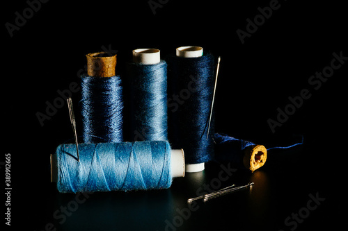 Reel with blue sewing silk threads and needles isolated on a black background, close-up, copy space Billede på lærred