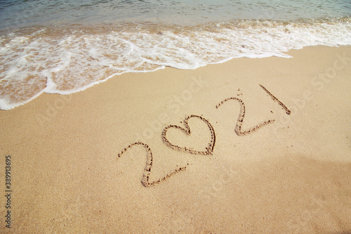 Foto Sign 2021 on the sand. Sign on the beach. New Year. seascape.