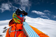 Leinwandbild Motiv Portrait of a stern climber skier in sunglasses and a cap with a ski mask on his face. holds his skis on his shoulder and looks away against of Mount Elbrus