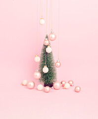 Christmas tree with ornaments over pink background. Minimal picture for winter holidays