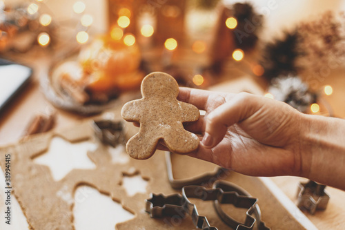 Obraz Person holding gingerbread man cookie on background of festive lights. Christmas tradition - fototapety do salonu