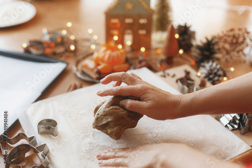 Tela Hands kneading raw gingerbread dough on background of metal cutters on rustic table